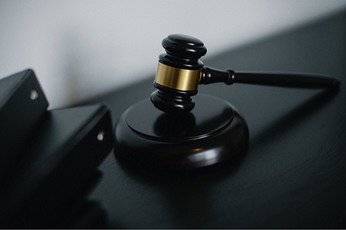 small-judge-gavel-placed-on-table-near-folders